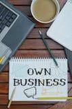 Arbeitsplatz mit Notizbuch mit Anmerkung ungefähr: Geschäft mit lapt besitzen Lizenzfreies Stockbild