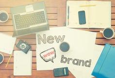 Arbeitsplatz mit Notizbuch mit Anmerkung ungefähr: Neue Marke mit Laptop Stockbilder
