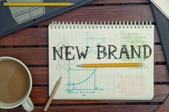 Arbeitsplatz mit Notizbuch mit Anmerkung ungefähr: Neue Marke mit Laptop Lizenzfreie Stockfotografie