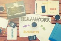 Arbeitsplatz mit Notizbuch mit Anmerkung ungefähr: Teamwork mit Laptop a Stockfoto