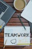 Arbeitsplatz mit Notizbuch mit Anmerkung ungefähr: Teamwork mit Laptop a Stockfotos