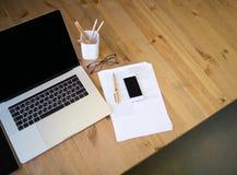 Arbeitsplatz mit offenen Laptop-Computer, zellulären und Papierdokumenten Stockfotos