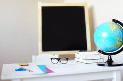 Arbeitsplatz mit Schulbank, Tafel, Kugel und Brillen Stockfoto