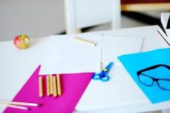 Arbeitsplatz mit Schulbedarf: Schreibtisch, Tafel, Kugel und Brillen Stockbild