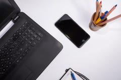 Arbeitsplatz mit schwarzer Laptop-Computer, intelligentes Telefon, Notizbuch und Stift und Kasten mit Farbstiften und -bleistifte Stockbilder