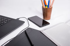 Arbeitsplatz mit schwarzer Laptop-Computer, Notizbuch, intelligentes Telefon, digitale grafische Tablette und Stift und Farbstift Stockbilder