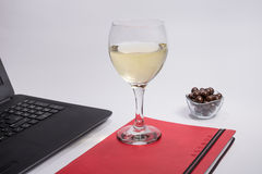 Arbeitsplatz mit schwarzer Laptop-Computer, Notizbuch, Schokoladenbällen und Glasweißwein auf weißem Hintergrund Lizenzfreie Stockfotografie