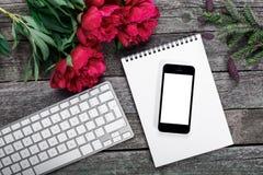 Arbeitsplatz mit Smartphone, Tastatur, Notizblock, Tannenzweig und Pfingstrosen blüht Blumenstrauß auf rustikalem Hintergrund Stockfoto