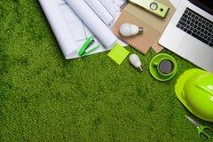 Arbeitsplatz mit Sturzhelm, Plänen, Laptop und Notizblock auf Gras b Lizenzfreies Stockfoto