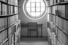 Arbeitsplatz mit Tabelle und Stuhl unter einem sonnigen Fenster umgeben durch Buchregale und Kilometer Archivkästen lizenzfreie stockbilder