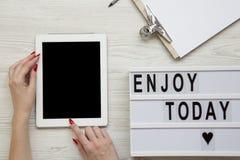 Arbeitsplatz mit Tablette, Notizblock und ` genießen heute ` Wort auf lightbox über weißem hölzernem Hintergrund, Ansicht von obe stockbild