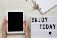 Arbeitsplatz mit Tablette, Notizblock und ` genießen heute ` Wort auf lightbox über weißem hölzernem Hintergrund, Draufsicht Weib stockfoto