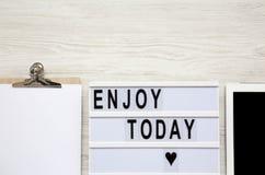 Arbeitsplatz mit Tablette, Notizblock und ` genießen heute ` Wort auf lightbox über weißer Holzoberfläche, Draufsicht Von oben Fl stockfotografie