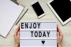 Arbeitsplatz mit Tablette, Smartphone, Notizblock und ` genießen heute ` Wort auf lightbox über weißem hölzernem Hintergrund, Dra lizenzfreie stockfotografie
