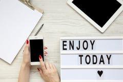 Arbeitsplatz mit Tablette, Smartphone, Notizblock und ` genießen heute ` Wort auf lightbox über weißem hölzernem Hintergrund, Dra stockbild