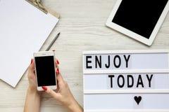 Arbeitsplatz mit Tablette, Smartphone, Notizblock und ` genießen heute ` Wort auf lightbox über weißem hölzernem Hintergrund, Dra stockbilder