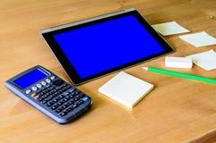Arbeitsplatz mit Tabletten-PC - blauer Kasten, Taschenrechner, Bleistift und stic Lizenzfreie Stockfotografie