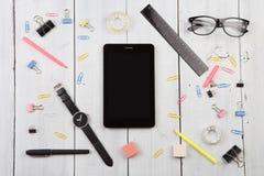 Arbeitsplatz mit Tabletten-PC, Gläser, Uhr, Stift stockbild