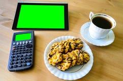 Arbeitsplatz mit Tabletten-PC - grüner Kasten, Taschenrechner, Tasse Kaffee Stockfotos