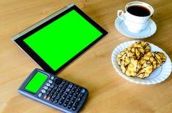 Arbeitsplatz mit Tabletten-PC - grüner Kasten, Taschenrechner, Tasse Kaffee Lizenzfreies Stockbild