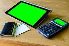 Arbeitsplatz mit Tabletten-PC - grüner Kasten, Taschenrechner und Geschäft c Lizenzfreie Stockfotos