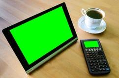Arbeitsplatz mit Tabletten-PC - grüner Kasten, Taschenrechner und Schale coff Stockbilder