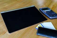 Arbeitsplatz mit Tabletten-PC, -taschenrechner und -Visitenkarte Stockfotografie