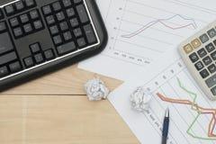 Arbeitsplatz mit Tastatur, Diagramm, Taschenrechner und Wanne auf hölzerner Tabelle Lizenzfreies Stockfoto