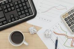 Arbeitsplatz mit Tastatur, Diagramm, Taschenrechner, Wanne und Kaffee Lizenzfreies Stockbild
