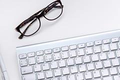 Arbeitsplatz mit Tastatur und Gläsern stockfotografie