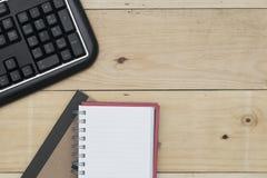 Arbeitsplatz mit Tastatur und Notizbuch auf hölzerner Tabelle Lizenzfreies Stockfoto