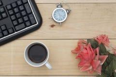 Arbeitsplatz mit Tastatur, Wecker, Kaffee und Blumen auf hölzerner Tabelle Stockbild