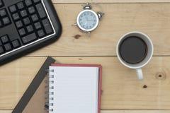 Arbeitsplatz mit Tastatur, Wecker, Kaffee und Notizbuch auf hölzerner Tabelle Stockbilder