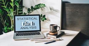 Arbeitsplatz ohne Leute, Nahaufnahme des Laptops mit statistischer Analyse der Aufschrift auf Schirm auf weißer Tabelle, Schreibt Stockfoto