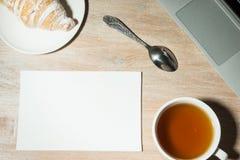 Arbeitsplatz zu Hause mit Laptop, Tee und Hörnchen Beschneidungspfad eingeschlossen Stockfotografie