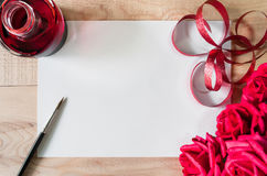 Arbeitsplatzaquarellpapier oder -Briefpapier mit roter Tinte, Bürste, rotem Band und Blumenstrauß von Rosen auf Holztisch Lizenzfreies Stockbild