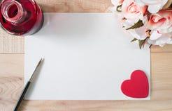 Arbeitsplatzaquarellpapier oder -Briefpapier mit roter Tinte, rotem Herzen, Bürste und Blumenstrauß von Rosen auf Holztisch Stockfotos