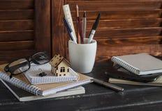 Arbeitsplatzdesigner und -architekt mit Geschäft wendet - Bücher, Notizbücher, Stifte, Bleistifte, Machthaber, Tablette, Gläser u Lizenzfreies Stockbild