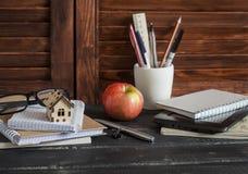 Arbeitsplatzdesigner und -architekt mit Geschäft wendet - Bücher, Notizbücher, Stifte, Bleistifte, Machthaber, Tablette, Gläser u Stockbild