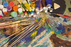 Arbeitsplatzmaler, bürsten in der Hand, Gläser mit Gouache, Segeltuch für Stockfotos