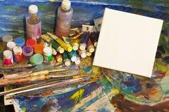 Arbeitsplatzmaler, bürsten in der Hand, Gläser mit Gouache, Segeltuch für Lizenzfreies Stockbild