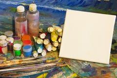 Arbeitsplatzmaler, bürsten in der Hand, Gläser mit Gouache, Segeltuch für Lizenzfreie Stockfotos