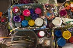 Arbeitsplatzmaler, bürsten in der Hand, Gläser mit Gouache, Segeltuch für das Malen, Palette, die Hintergrundkunst Lizenzfreie Stockfotografie