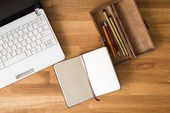 Arbeitsplatzmodell mit Notizbuch, Laptop und Bleistift Lizenzfreie Stockfotos