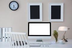 Arbeitsplatzrechner auf Schreibtisch mit Bilderrahmen auf Wand Stockfotos