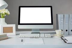 Arbeitsplatzrechner mit Bilderrahmen und Tasse Kaffee Stockfotografie