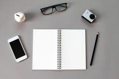 Arbeitsplatzschreibtisch mit leerem Notizbuch, Bleistift, Augengläsern, kleiner Aktionskamera, Sparschwein und intelligentem Tele Lizenzfreies Stockbild