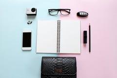 Arbeitsplatzschreibtisch mit leerem Notizbuch, Bleistift, Lippenstift, Autoschlüssel, Augengläsern, kleiner Aktionskamera, Ohrrin Stockfotografie