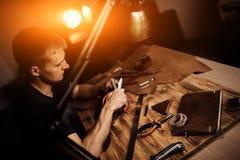 Arbeitsprozeß des Ledergürtels in der ledernen Werkstatt Mann, der das In Handarbeit machen des Werkzeugs und das Arbeiten hält G Stockfotografie