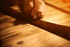 Arbeitsprozeß des Ledergürtels in der ledernen Werkstatt Mann, der das In Handarbeit machen des Werkzeugs und das Arbeiten hält G Stockbilder
